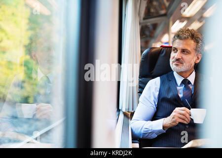 Man with coffee voyageant en train. Banque D'Images