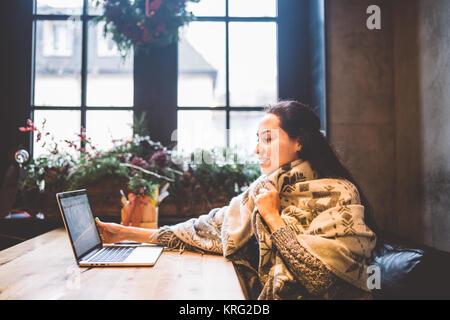 Belle jeune fille utilise la technologie de l'ordinateur portable, les types de texte le moniteur dans un café au Banque D'Images