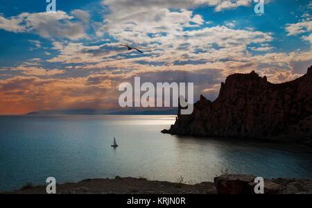 Paysage du soir avec le coucher du soleil et nuages sur une mer calme, les falaises, les mouettes et un voilier, Crimée, Novy Svet.