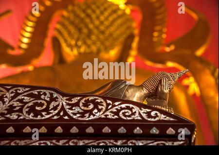 Statue de Bouddha en bronze dans la posture couchée avec main droite soutenant la tête, allongé sur un lit en bois Banque D'Images