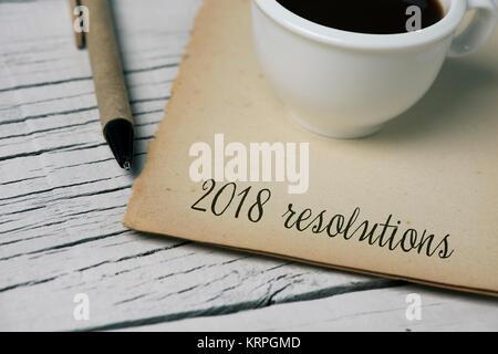 Le texte des résolutions 2018 dans une note de couleur jaunâtre, une tasse de café et d'un stylo, sur une table Banque D'Images