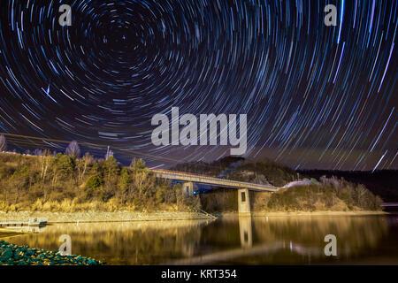 Star Trails révèlent la rotation de la terre au-dessus de la surface d'un lac. Banque D'Images
