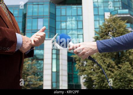 Interview journaliste d'affaires, bâtiment d'entreprise en arrière-plan Banque D'Images