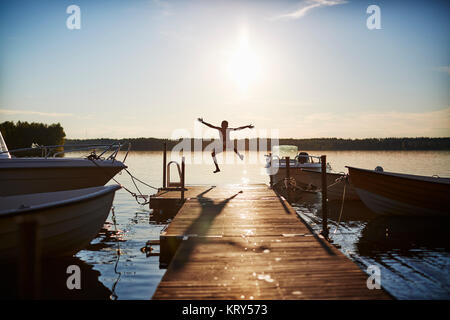 Boy jumping on a pier Banque D'Images