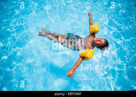 Un garçon portant des ailes de l'eau flottant dans une piscine Banque D'Images