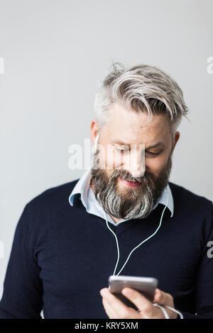 Un homme avec les casques dans l'écoute de son téléphone cellulaire