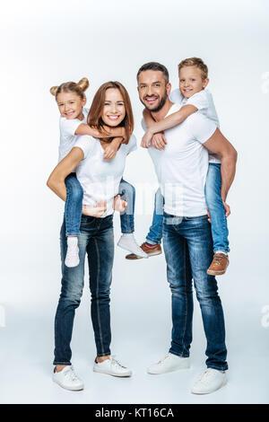 Les parents sur le dos des enfants heureux Banque D'Images