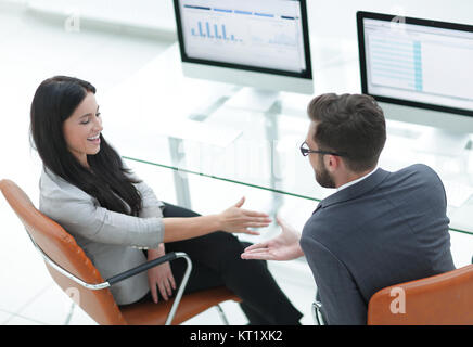 Les membres de l'équipe commerciale se donnent cinq, assis au bureau
