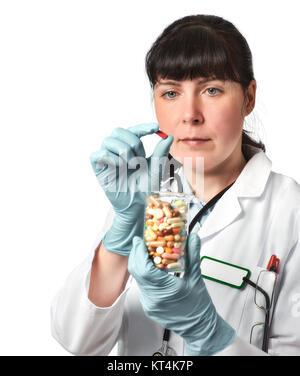 Femme médecin ou infirmière avec le verre plein de comprimés dans une main gantée tenant une pilule rouge au forceps. Banque D'Images