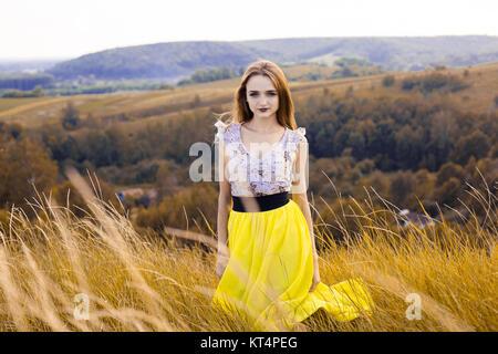 Belle fille à la mode très belle robe à fleurs sur le terrain. Belle fille avec gerbe de fleurs sur sa tête et bouquet Banque D'Images