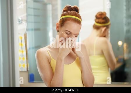 Redhead girl applying lipstick in accueil salle de bains au matin. Jeune femme en prenant soin de sa peau, à sourire Banque D'Images