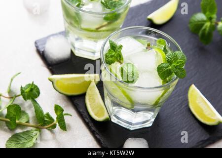 Rempli de limonade d'été mojito dans un verre sur un fond noir en ardoise et du conseil.