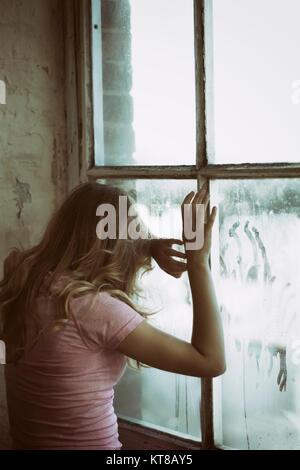 Vue arrière d'une femme blonde debout près de la fenêtre les mains de toucher le verre Banque D'Images