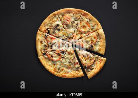 Pizza italien frais avec champignons, tomates, fromage, sur fond noir en noir Banque D'Images