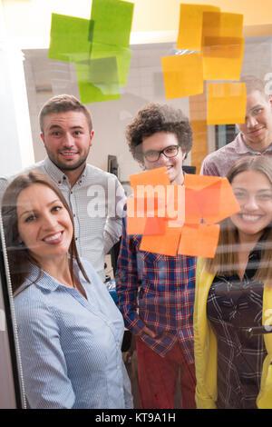 Les jeunes gens d'affaires de démarrage créative sur réunion au bureau moderne à faire des plans et des projets avec des autocollants sur verre post