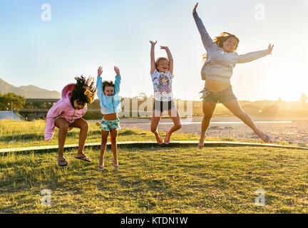 Quatre heureux Jeunes filles sautant en l'air au crépuscule Banque D'Images