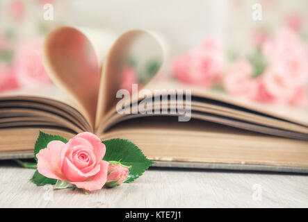 Pages d'un vieux livre panneaux en forme de coeur et peu de roses sur la table en bois. Carte de Saint-Valentin. Banque D'Images