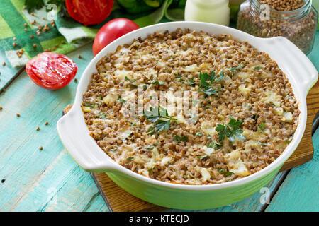 Casserole de poisson au sarrasin et divers légumes verts et sur une table en bois de cuisine. Banque D'Images