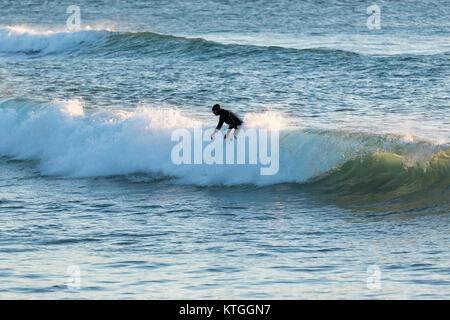 Surfer sur la plage de Fistral, Newquay, Cornwall, UK dans une mer froide au coucher du soleil