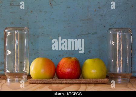 Trois pommes de couleur sur une serviette en lin entre les pots de verre sur le fond de l'ancien mur bleu. Espace Banque D'Images