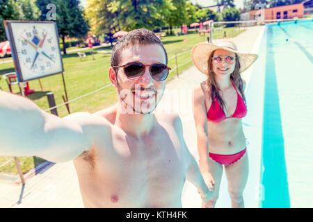 Jeune couple d'amoureux au bord de la piscine prend un maillot en selfies. Concept de jeunes s'amusant en été Banque D'Images