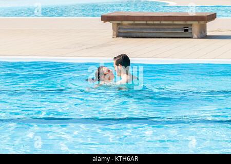 Jeune couple aimant baisers et se détend dans la piscine d'hydromassage Banque D'Images