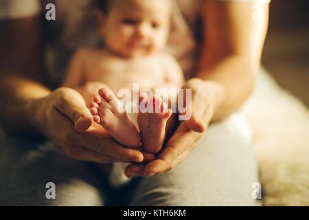 Baby les mains. Les pieds de bébé nouveau-né sur les mains Banque D'Images