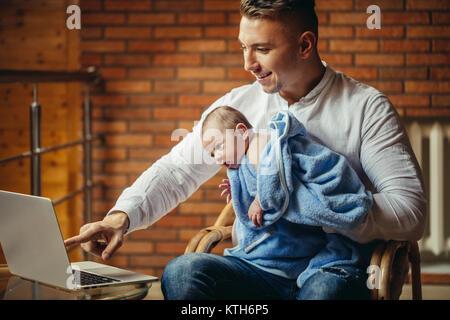 Père avec nouveau-né travailler à domicile à l'aide de coffre Banque D'Images