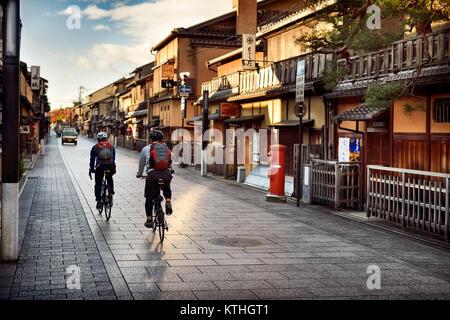 Les cyclistes sur une case vide Hanamikoji Dori street dans le quartier de Gion, le matin avant le lever du soleil Banque D'Images