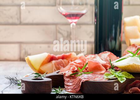 Concept de la cuisine italienne avec du vin rouge, de melon et de jambon sur une planche à découper Banque D'Images