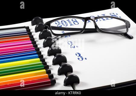 Objectifs 2018 texte sur le carnet avec stylo de couleur blanche et lunettes Banque D'Images