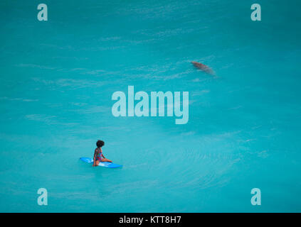 Surfer Girl avec coiffure afro assis sur une planche de surf dans l'eau vert clair à la vache en mer à la plage Banque D'Images
