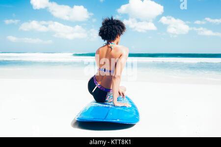 Surfer Girl avec coiffure afro assis à côté de blue surf sur la plage de sable blanc en face d'un paysage marin Banque D'Images