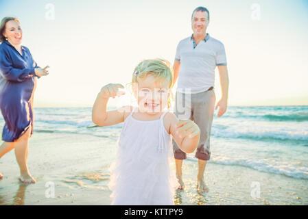 Laughing baby girl en marche avant avec smiling parents sur l'arrière-plan. Le bonheur et l'harmonie dans la vie Banque D'Images