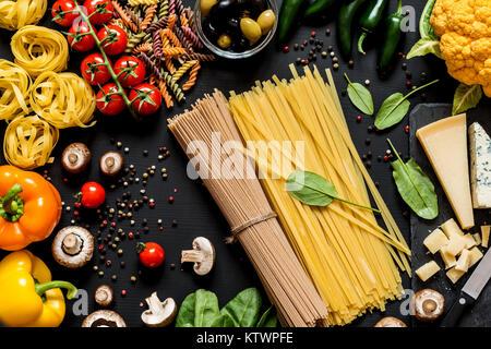 Différents ingrédients frais pour les pâtes italiennes, spaghetti, fettuccine, fusilli et légumes sur un fond noir. Mise à plat, vue du dessus.