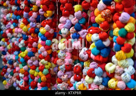 Boules de tissu coloré, des singes Kukurizaru lié avec pieds, représentant le contrôle des désirs en échange de Banque D'Images