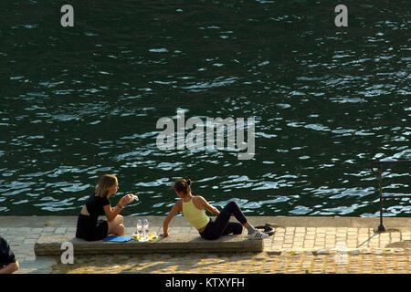 Les jeunes ayant pic-nick en début de soirée sur les bords de Seine, dans l'île Saint-Louis Banque D'Images