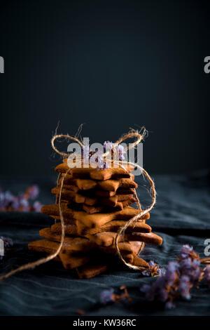 En forme d'étoile de pile liée gingerbread cookies. Décorées avec des fleurs séchées, un arrière-plan sombre. Banque D'Images