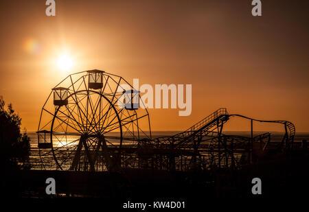 Coucher du soleil vu de la grande roue et les montagnes russes Banque D'Images