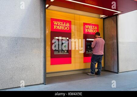 Un homme utilise un Wells Fargo Guichet automatique bancaire (GAB) à l'extérieur du siège de la Wells Fargo Capital Banque D'Images