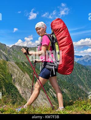 La randonnée. Sac à dos de voyageur avec de grandes promenades le long du bord du col à l'aide de bâtons de trekking Banque D'Images