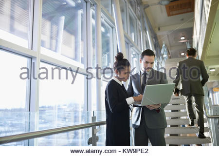Businessman and businesswoman using laptop in office lobby Banque D'Images