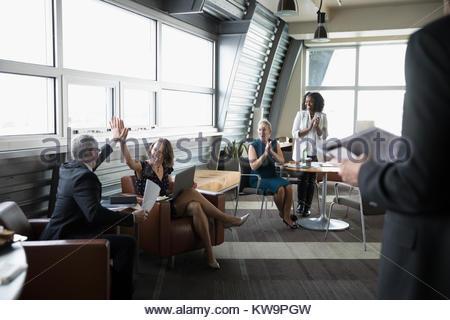 Les gens d'affaires célèbre,haute-fiving dans un salon d'affaires Banque D'Images
