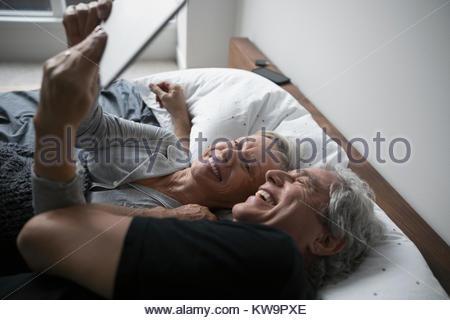 Affectueux,happy senior couple with digital tablet selfies,câlins au lit Banque D'Images