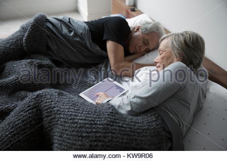 Senior woman relaxing,using digital tablet à côté de mari dormir au lit Banque D'Images