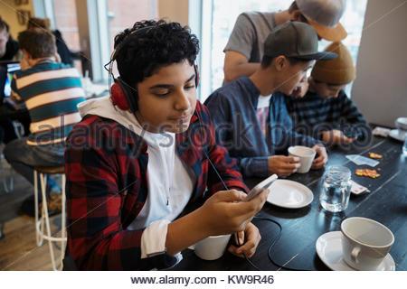 Tween moyen-orientale garçon avec des écouteurs lorsque vous écoutez de la musique avec smart phone at cafe table Banque D'Images