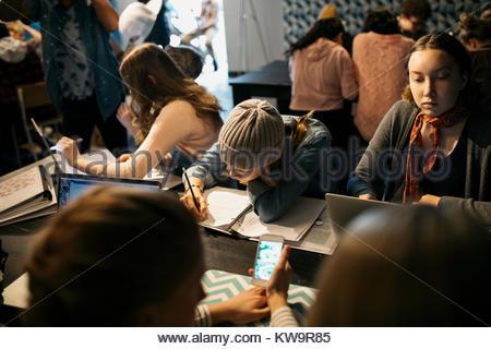 Les élèves du secondaire l'étude,la prise de notes et l'utilisation d'ordinateur portable et smart phone in cafe Banque D'Images
