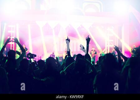 Silhouettes de concert foule à Vue arrière de festivaliers lèvent la main sur stage lights lumineux