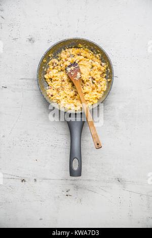 Du jambon et des œufs. Oeufs brouillés avec bacon dans pan en céramique. Banque D'Images
