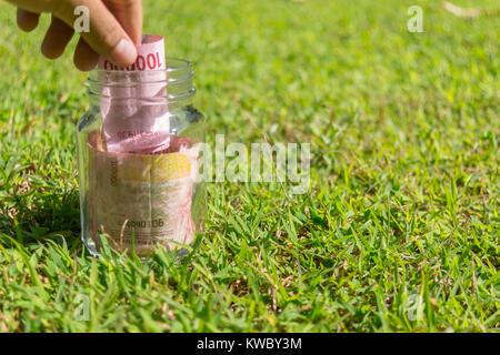 Cent mille roupies, la monnaie de papier dans le bocal sur la nature de fond vert